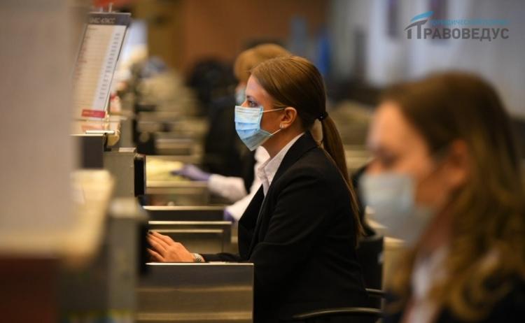 Девушка в маске, сидящая на рабочем месте